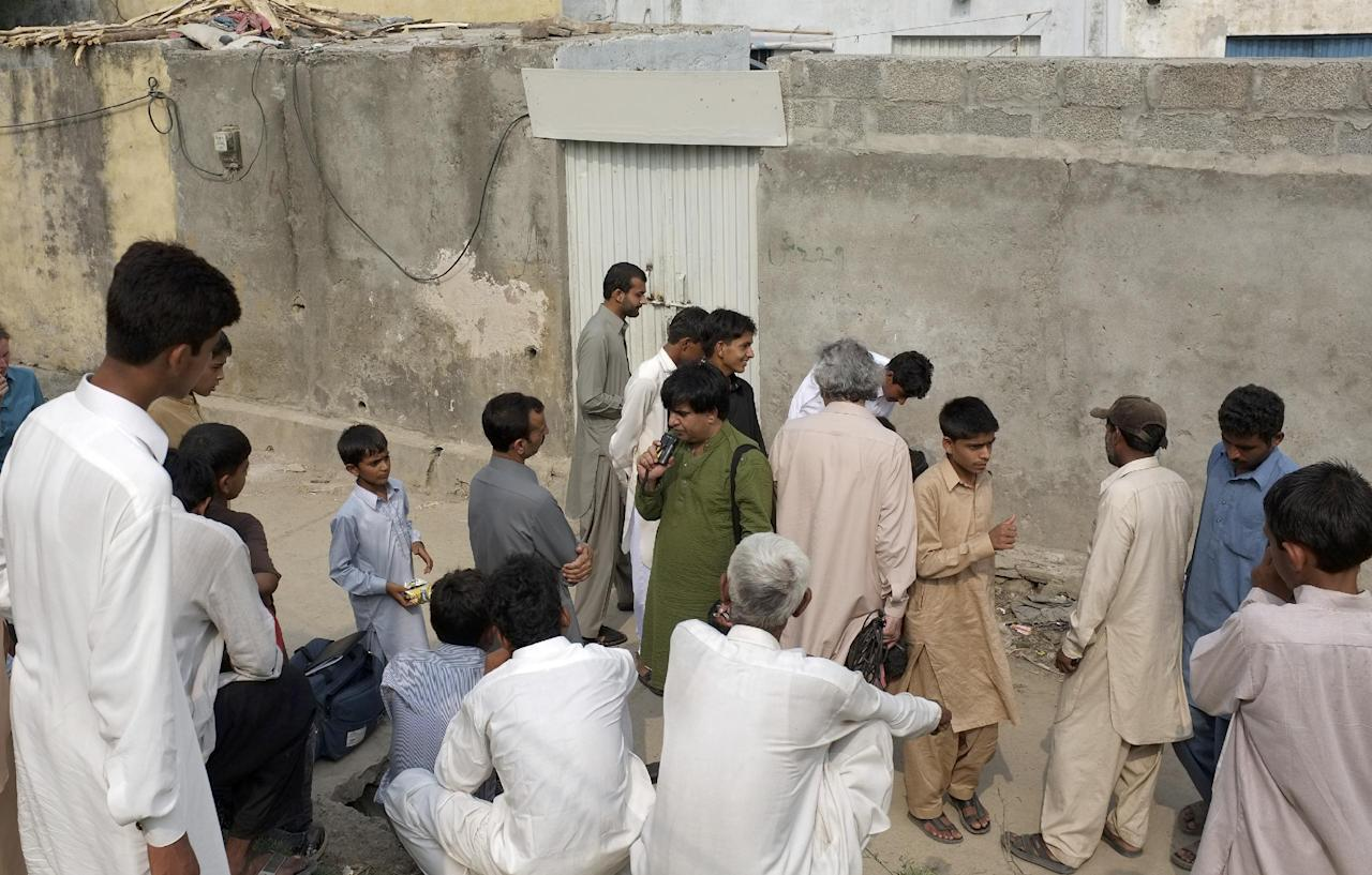 People gathered outside the locked house of a Christian girl in suburbs of Islamabad, Pakistan on Monday, Aug. 20, 2012. Pakistani authorities arrested a Christian girl and are investigating whether she violated the country's strict blasphemy laws after furious neighbors surrounded her house and demanded police take action, a police officer said Monday. The arrest of the girl and outrage among the local community demonstrates the deep emotion that suspected blasphemy cases can evoke in this conservative Muslim country, where rising extremism often means religious minorities live in fear of persecution.(AP Photo/B.K. Bangash)