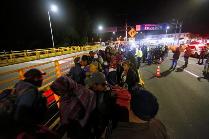 Stranded migrants are pictured at Rumichaca International Bridge between Colombia and Ecuador, after Ecuador's government closed its borders to all foreign travelers due to the spread of the coronavirus disease (COVID-19), in Tulcan