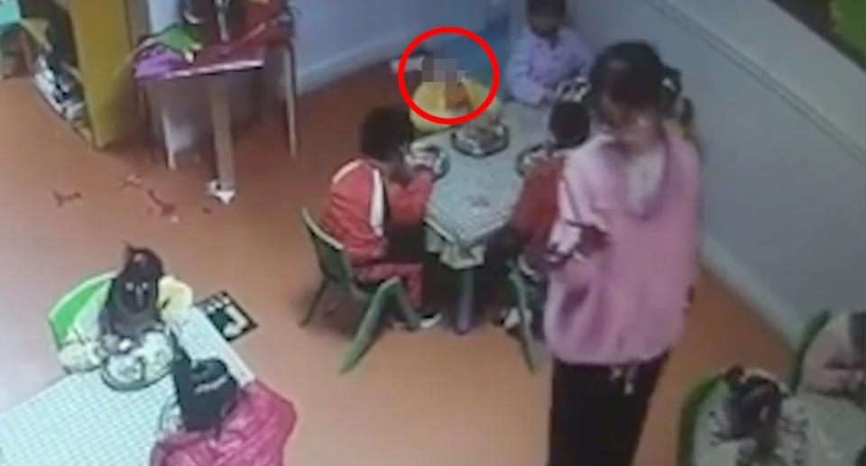 A child's head, which is circled in this photo, is seen falling backwards as a teacher films other students on her mobile phone.