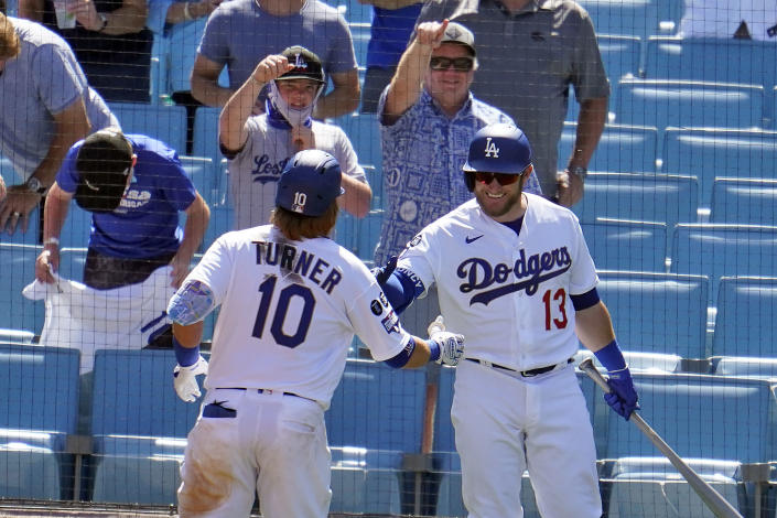 Los Angeles Dodgers' Justin Turner (10) is congratulated by Max Muncy (13) after hitting a solo home run in the sixth inning of a baseball game against the Washington Nationals, Friday, April 9, 2021, in Los Angeles. (AP Photo/Marcio Jose Sanchez)