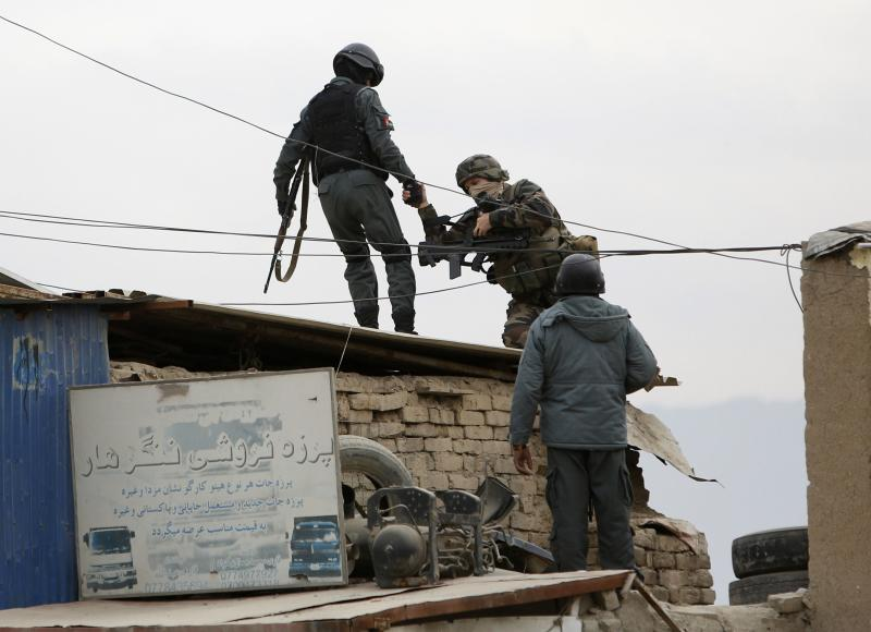 An Afghan policeman helps a serviceman from International Security Assistance Force at the site of a bomb attack in Kabul