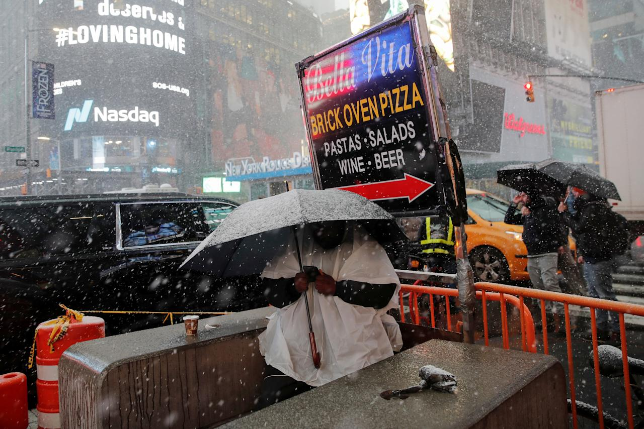 A man sits under an umbrella during a snowstorm in Times Square in New York City, New York, U.S., November 15, 2018. REUTERS/Mike Segar     TPX IMAGES OF THE DAY