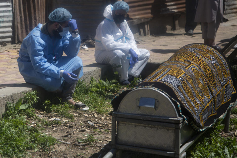 Relatives mourn near a coffin containing the body of a person who died of COVID-19 in Srinagar, Indian controlled Kashmir, Sunday, April 25, 2021. India's crematoriums and burial grounds are being overwhelmed by the devastating new surge of infections tearing through the populous country with terrifying speed, depleting the supply of life-saving oxygen to critical levels and leaving patients to die while waiting in line to see doctors. (AP Photo/Mukhtar Khan)