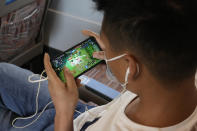 A man plays the popular Honor of Kings online game from Chinese gaming platform Tencent during a high speed train from Henan to Beijing Wednesday, Sept. 15, 2021. China has set new rules limiting the amount of time kids can spend playing online games. (AP Photo/Ng Han Guan)