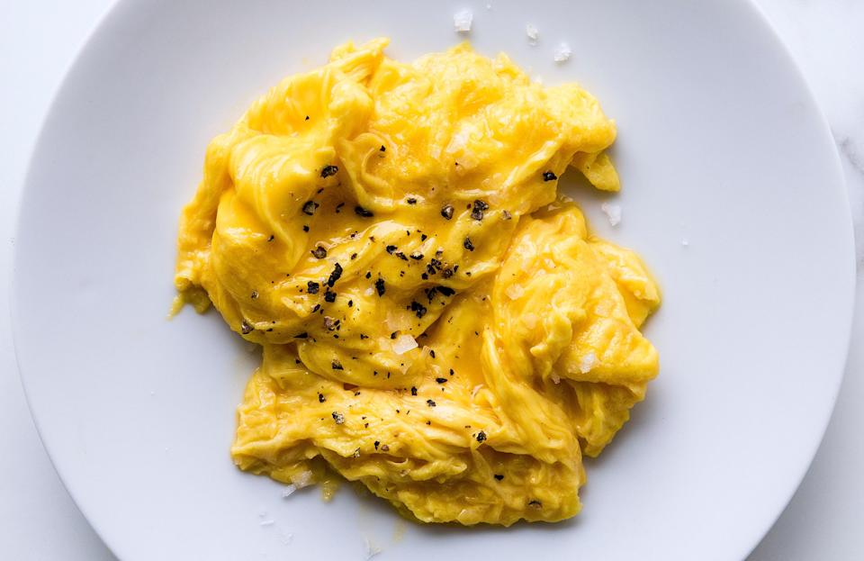 """Medium-low heat is the key to the fluffy, creamy, melty texture of these scrambled eggs. <a href=""""https://www.bonappetit.com/recipe/bas-best-soft-scrambled-eggs?mbid=synd_yahoo_rss"""" rel=""""nofollow noopener"""" target=""""_blank"""" data-ylk=""""slk:See recipe."""" class=""""link rapid-noclick-resp"""">See recipe.</a>"""