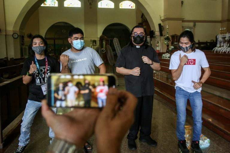 TikTok is playing a central role in Father Paul Woo's (2nd R) efforts to coax the young into church pews in Navotas City, one of the poorest areas of the Philippines' capital