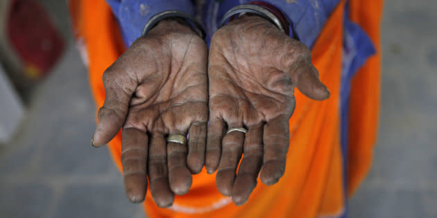 Radha, 75, a vegetable vendor, poses with her hands after she got her fingerprint scanned for the Unique Identification (UID) database system at an enrolment centre at Merta district in the Indian state of Rajasthan on February 22, 2013.