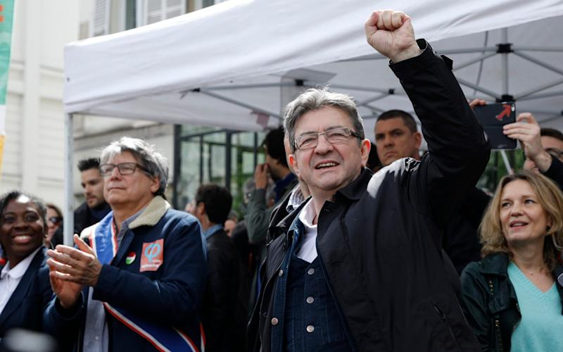 Jean-Luc Melenchon, a former hard-left candidate in the first round of the presidential election, clenches his fist during the May Day demonstration - Credit: Kamil Zihnioglu/AP