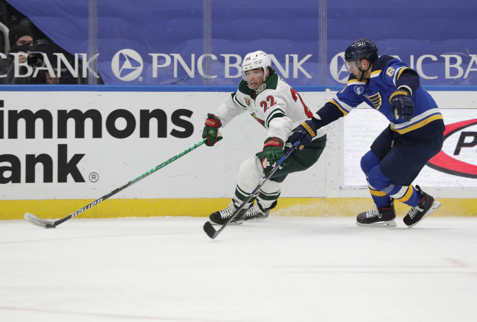 Minnesota Wild's Kevin Fiala (22) fights off St. Louis Blues' Marco Scandella (6) as he skates with the puck in the first period of an NHL hockey game, Wednesday, May 12, 2021 in St. Louis. (AP Photo/Tom Gannam)