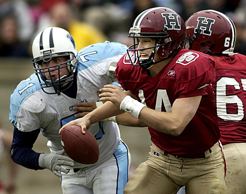Harvard University quarterback Ryan Fitzpatrick scrambles away from Columbia University's Clint Eberlin during the first half of their game, Saturday Nov. 6, 2004, in Boston at Harvard Stadium. (AP Photo/Adam Hunger)
