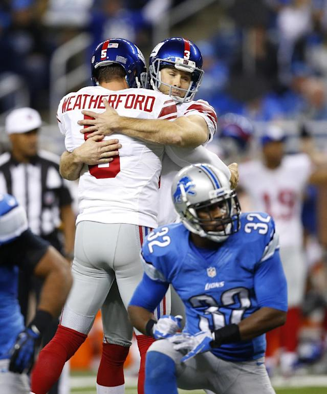 New York Giants kicker Josh Brown, facing camera, is hugged by holder Steve Weatherford (5) after Brown's 45-yard field goal in overtime to defeat the Detroit Lions 23-20 in an NFL football game in Detroit, Sunday, Dec. 22, 2013. The Lions are eliminated from postseason contention. (AP Photo/Rick Osentoski)