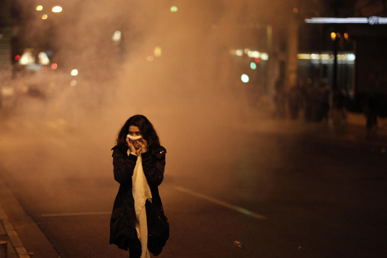 A pedestrian covers her face to protect from tear gas during a protest in front of the Greek parliament in Athens, Wednesday, April 4, 2012.  A Greek retiree shot himself dead in Athens' main square Wednesday, blasting politicians over the country's financial crisis in a suicide note that triggered violent clashes hours later between police and anti-austerity protesters. (AP Photo/Kostas Tsironis)