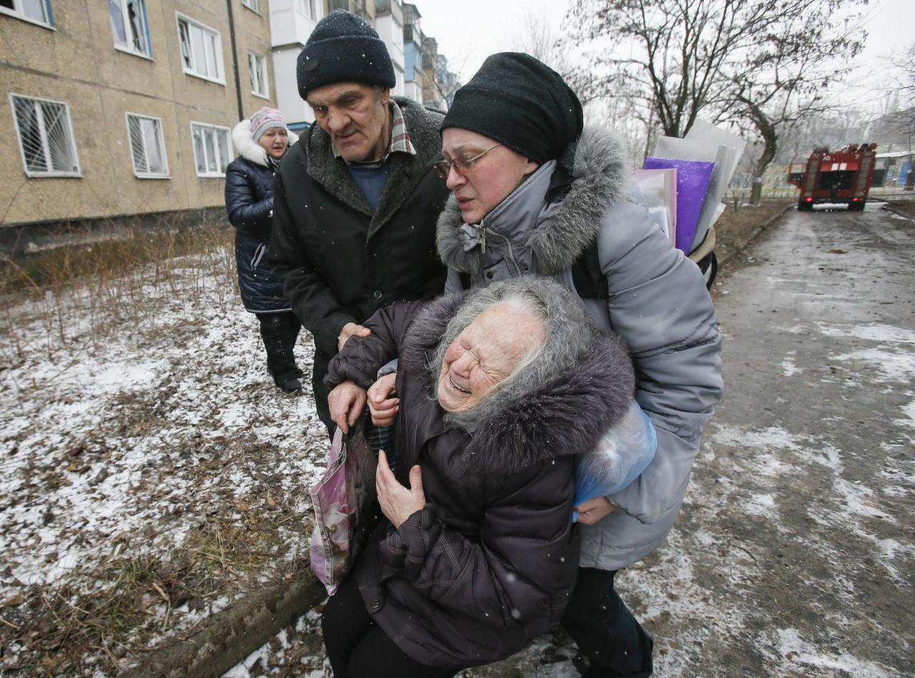 An elderly woman reacts after the residential block in which she lives in was damaged by a recent shelling, according to locals, on the outskirts of Donetsk, eastern Ukraine February 9, 2015. REUTERS/Maxim Shemetov (UKRAINE - Tags: POLITICS CIVIL UNREST CONFLICT TPX IMAGES OF THE DAY)