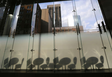 The shadows of tables and chairs are cast on frosted glass from the reflected late afternoon sunlight shining from a nearby tower in Toronto