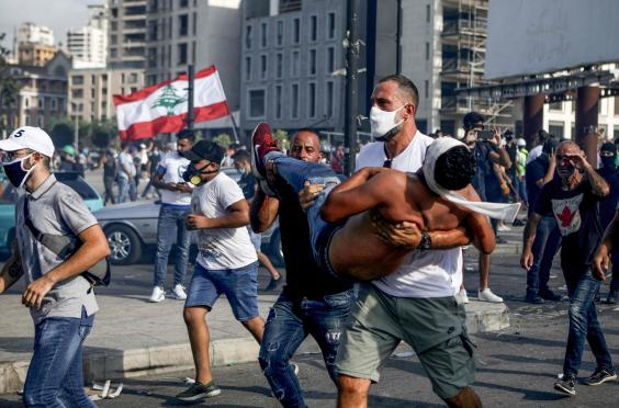 A Lebanese protester carries a wounded demonstrator away from clashes in downtown Beirut (AFP/Getty)