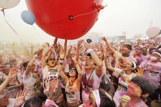 Participants covered with colour powder play with a giant balloon during a five-kilometre colour run event in Beijing June 21, 2014. REUTERS/China Daily (CHINA - Tags: SPORT ATHLETICS SOCIETY) CHINA OUT. NO COMMERCIAL OR EDITORIAL SALES IN CHINA