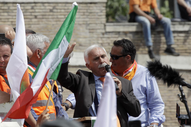 Leader of the Orange Vests movement, Antonio Pappalardo, addresses a rally in Rome, Tuesday, June 2, 2020. Hundreds of protesters shunning masks gathered in Rome's Piazza del Popolo on Tuesday to demonstrate against the government measures taken to stop the spread of coronavirus. The so-called Orange Vests, a marginal political movement created last year by a retired Carabinieri general, have emerged as virus-denial camp in Italy, the first Western country to be hit by the global pandemic. (AP Photo/Alessandra Tarantino)