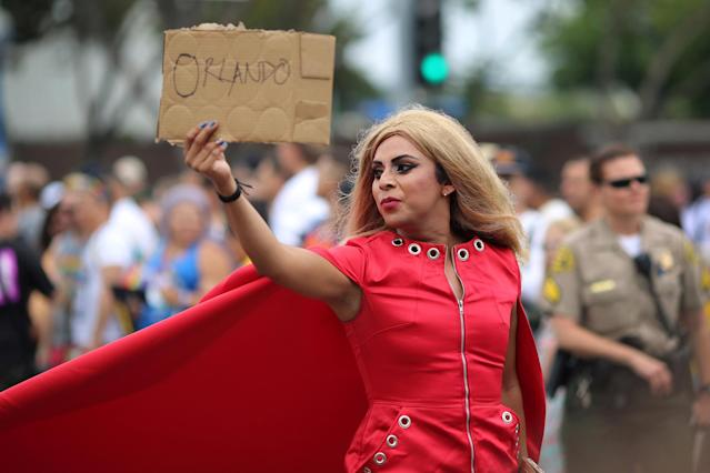 <p>A parade marcher holds a sign in memory of the victims of the attack on a gay night club in Orlando, Florida at the 46th annual Los Angeles Gay Pride Parade in West Hollywood, California, June 12, 2016. (REUTERS/David McNew) </p>
