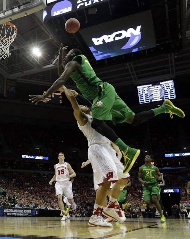 Oregon forward Richard Amardi, right, goes up for a shot over Wisconsin guard Traevon Jackson during the first half of a third-round game of the NCAA college basketball tournament Saturday, March 22, 2014, in Milwaukee. (AP Photo/Morry Gash)