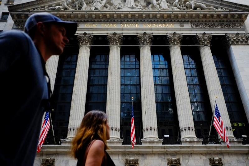 People walk by New York Stock Exchange in the financial district in New York