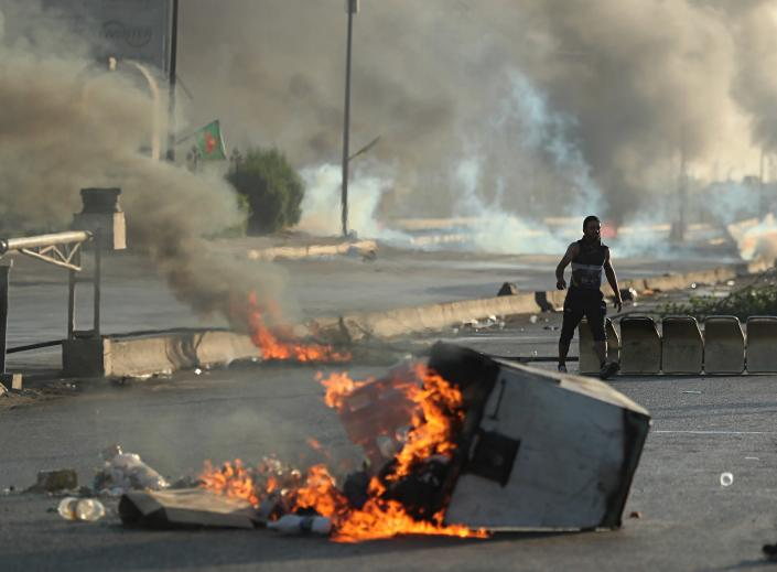 Anti-government protesters set fires and close a street during a demonstration in Baghdad, Iraq, Saturday, Oct. 5, 2019. Iraqi protesters pressed on with angry anti-government rallies across several provinces, in some cases torching party offices, for the fifth day, ignoring appeals for calm from political and religious leaders. Security agencies kept up their heavy crackdown, firing live ammunition and killing more than 14 protesters Saturday. (AP Photo/Hadi Mizban)