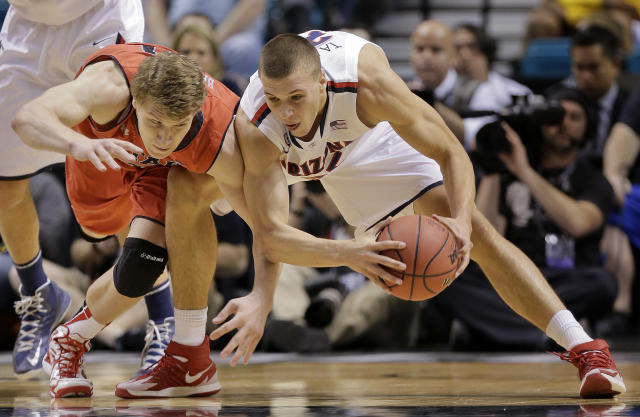 Utah's Dallin Bachynski, left, and Arizona's Kaleb Tarczewski scramble for a loose ball during the first half of an NCAA college basketball game in the quarterfinals of the Pac-12 Conference tournament, Thursday, March 13, 2014, in Las Vegas. (AP Photo/Julie Jacobson)
