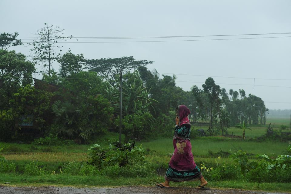 A woman walks along a road under the rain ahead of the expected landfall of cyclone Amphan in Midnapore, West Bengal, on May 20, 2020. (Photo by DIBYANGSHU SARKAR/AFP via Getty Images)