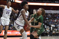 Connecticut's Christyn Williams, front left, strips the ball from South Florida's Elena Tsineke, right, during the first half of an NCAA college basketball game in the American Athletic Conference tournament semifinals at Mohegan Sun Arena, Sunday, March 8, 2020, in Uncasville, Conn. (AP Photo/Jessica Hill)