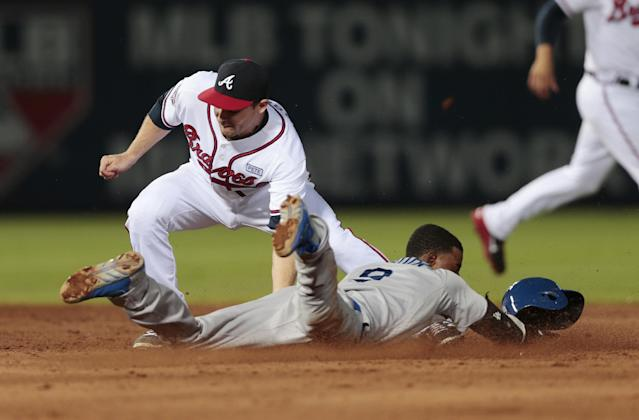 Los Angeles Dodgers' Dee Gordon (9) steals second base as Atlanta Braves second baseman Phil Gosselin (15) applies the late tag in the fifth inning of a baseball game Wednesday, Aug. 13, 2014, in Atlanta. (AP Photo/John Bazemore)