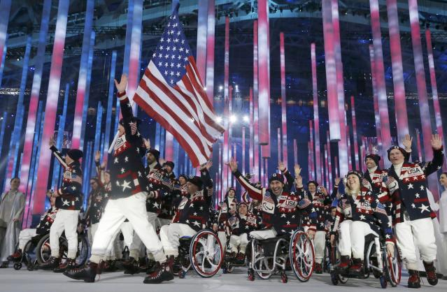 Flag-bearer Jonathan Lujan of the U.S. (2ndL), leads his country's contingent during the opening ceremony of the 2014 Paralympic Winter Games in Sochi, March 7, 2014. REUTERS/Alexander Demianchuk (RUSSIA - Tags: OLYMPICS SPORT)