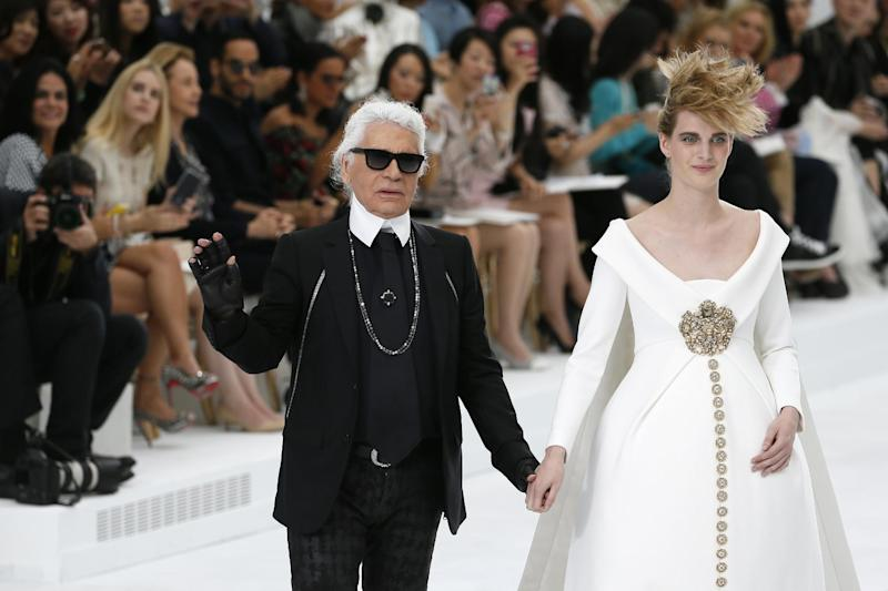 German fashion designer Karl Lagerfeld acknowledges the public with a model at the end of the Chanel 2014/2015 Haute Couture Fall-Winter collection fashion show on July 8, 2014 at the Grand Palais in Paris (AFP Photo/Patrick Kovarik)