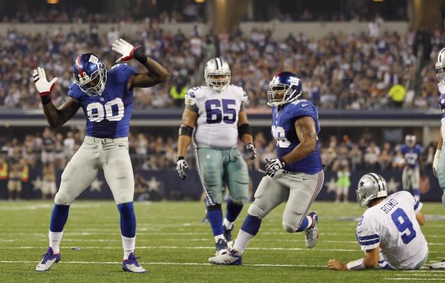 New York Giants defensive end Jason Pierre-Paul (L) celebrates after sacking Dallas Cowboys quarterback Tony Romo (R) next to Cowboys guard Ronald Leary (2nd L) and Giants defensive tackle Cullen Jenkins in the second half of their NFL football game in Arlington, Texas September 8, 2013. REUTERS/Mike Stone (UNITED STATES - Tags: SPORT FOOTBALL)