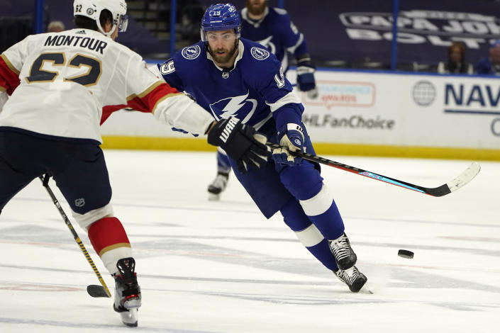 Tampa Bay Lightning right wing Barclay Goodrow (19) dumps the puck past Florida Panthers defenseman Brandon Montour (62) during the second period in Game 6 of an NHL hockey Stanley Cup first-round playoff series Wednesday, May 26, 2021, in Tampa, Fla. (AP Photo/Chris O'Meara)