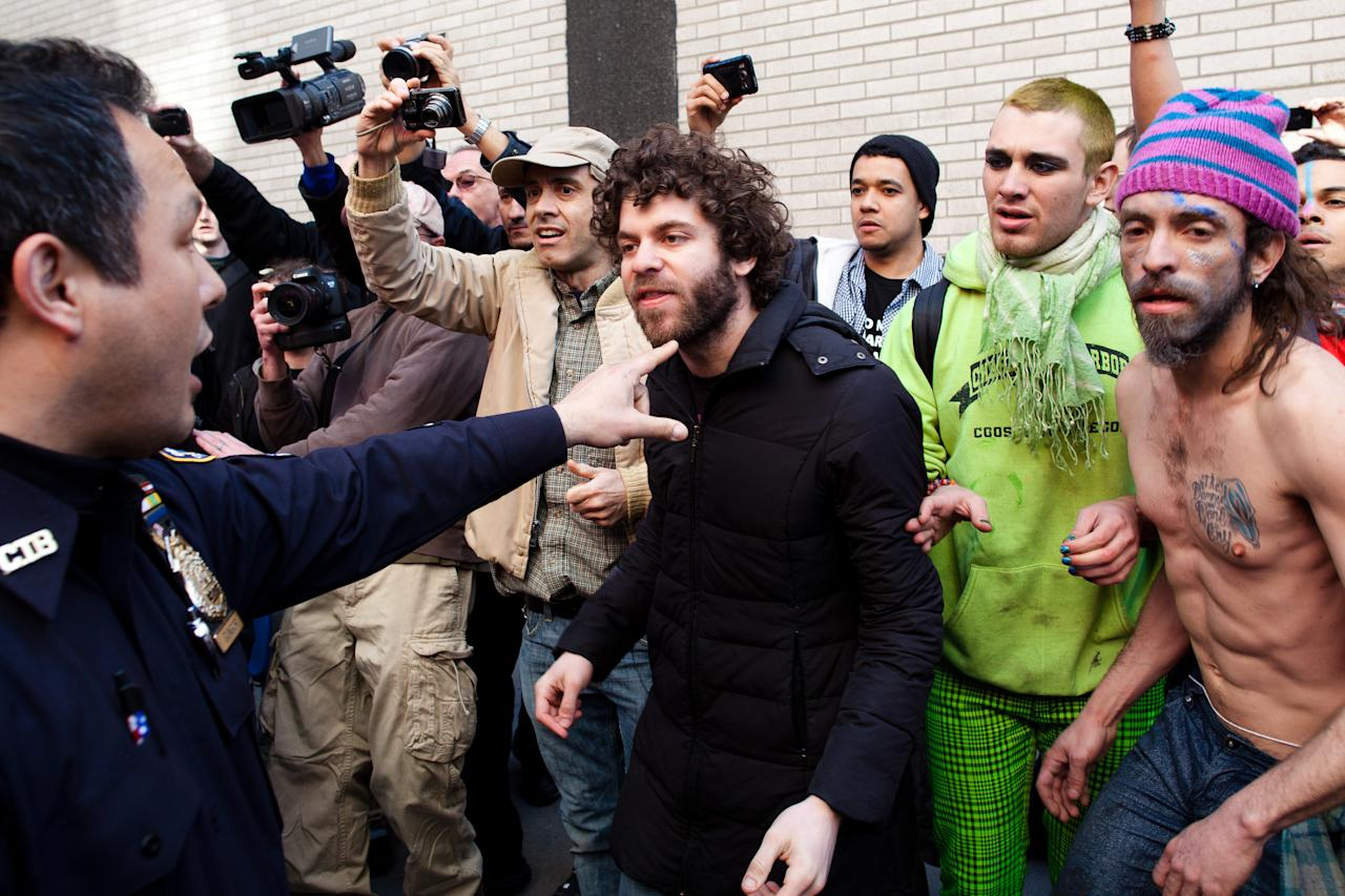 An Occupy Wall Street demonstrator is pushed back from the scene of an arrest by a police officer after a march in celebration of the protest's sixth month, Saturday, March 17, 2012, in New York. With the city's attention focused on the huge St. Patrick's Day Parade many blocks uptown, the Occupy rally drew a far smaller crowd than the demonstrations seen in the city when the movement was at its peak in the fall. (AP Photo/John Minchillo)