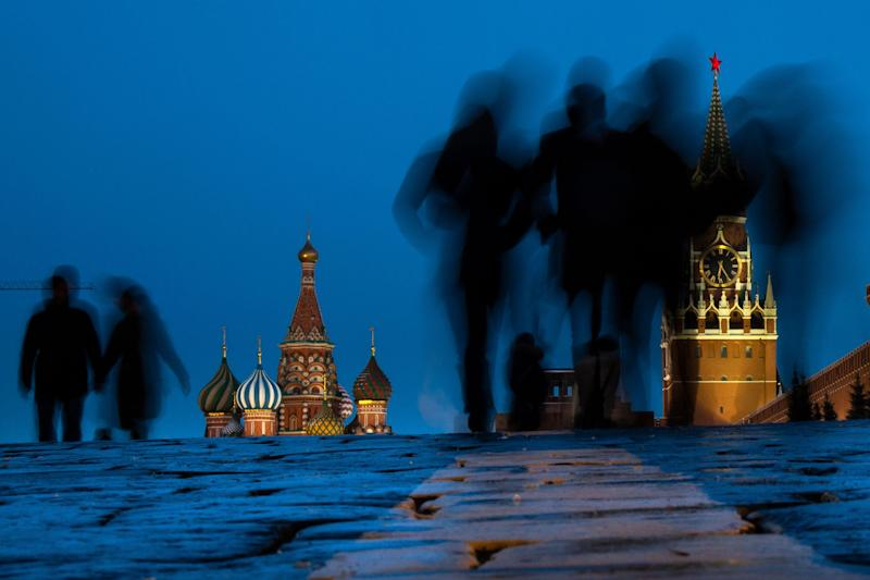 People walk through Red Square after sunset in Moscow, Russia, March 3, 2019, with the St. Basil's background left, and the Spasskaya Tower, right, in the background. (Photo: Alexander Zemlianichenko/AP)