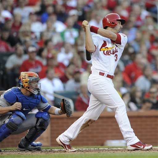 St. Louis Cardinals' Matt Carpenter, right, watches his RBI single as New York Mets' John Buck looks on in the second inning in a baseball game Monday, May 13, 2013, at Busch Stadium in St. Louis. (AP Photo/Bill Boyce)