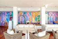 """<p>Okay, we admit, this one is a bit of a cheat, but a multicolor mural or wallcovering is the ultimate way to usher positivity into your home. We are inspired by this lobby wall at <a href=""""https://www.verywellmind.com/the-color-psychology-of-yellow-2795823"""" rel=""""nofollow noopener"""" target=""""_blank"""" data-ylk=""""slk:Casa Angelina"""" class=""""link rapid-noclick-resp"""">Casa Angelina</a>, an award-winning hotel on the Amalfi Coast, that is perfectly juxtaposed with the rest of the decor. While the natural fibers and colors of the furniture and flooring pay homage to the Mediterranean's breezy aesthetic, this rainbow wall hints at the hotel's fabulous contemporary art collection and invites guests to have the experience of a lifetime. </p>"""