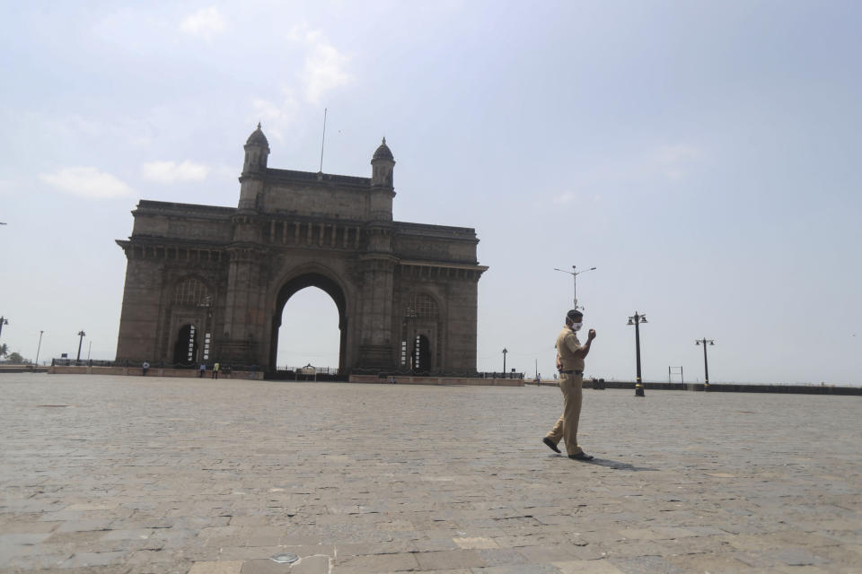 An Indian police officer wearing mask patrols at the Gateway of India in Mumbai, India, Monday, April 5, 2021. India reported its biggest single-day spike in confirmed coronavirus cases since the pandemic began Monday, and officials in the hard-hit state home to Mumbai are returning to the closure of some businesses and places of worship in a bid to slow the spread. (AP Photo/Rafiq Maqbool)