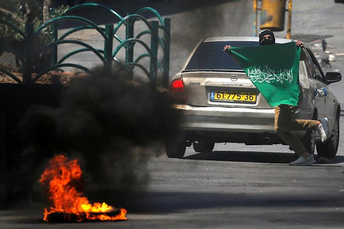 A Palestinian demonstrator holds a Hamas flag as he runs during a protest over cross-border violence between Palestinian militants in Gaza and the Israeli military, in Hebron, in the Israeli-occupied West Bank on May 18, 2021. / Credit: MUSSA ISSA QAWASMA/REUTERS