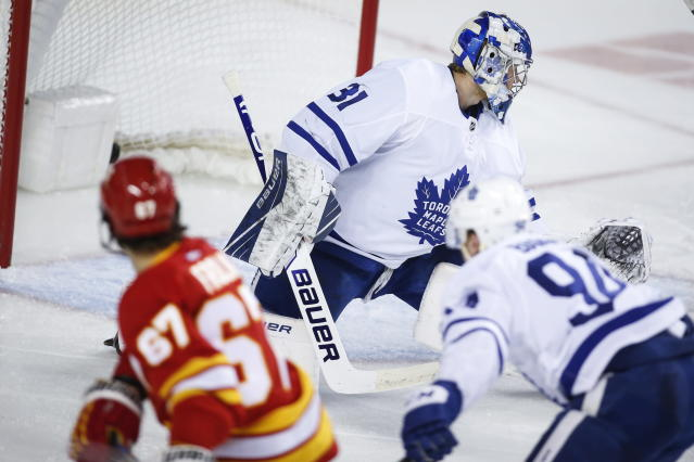 Toronto Maple Leafs goalie Frederik Andersen, right, looks back at the net as Calgary Flames' Michael Frolik scores during the third period of an NHL hockey game, Thursday, Dec. 12, 2019 in Calgary, Alberta. (Jeff McIntosh/The Canadian Press via AP)