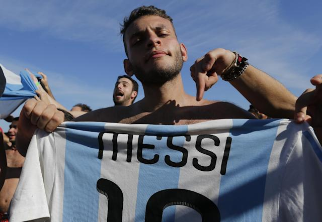 A soccer fan of the Argentina national soccer team poses with a Messi soccer jersey on Copacabana beach, in Rio de Janeiro, Brazil, Saturday, July 5, 2014. Argentina defeated Belgium 1-0 to reach the World Cup semifinals for the first time since 1990. (AP Photo/Silvia Izquierdo)