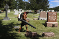Steve Rodriguez works in the St. Joseph's Cemetery Tuesday, June 15, 2021, in Galesburg, Ill. Settled more than 180 years ago, Galesburg was built around Knox College, founded by Presbyterians from upstate New York seeking a Christian school on the western frontier. The city soon became home to Illinois' first anti-slavery society. (AP Photo/Shafkat Anowar)