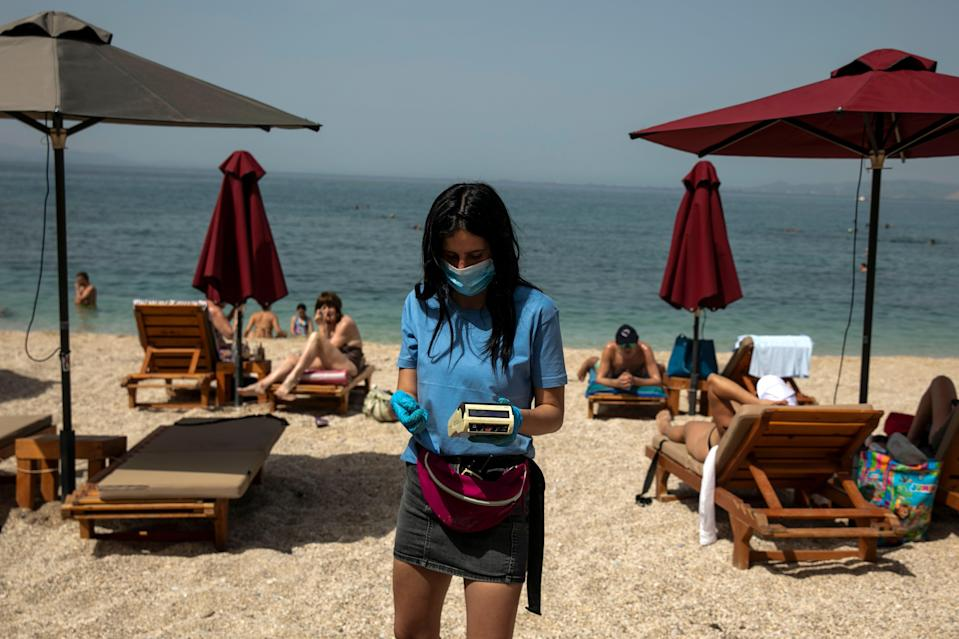 <p>An employee on a beach in Greece</p> (AP)