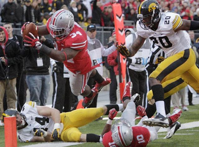 Ohio State running back Carlos Hyde, top, dives over the goal line to score a touchdown past teammate Corey Brown, bottom right, and Iowa defenders James Morris, left, and Christian Kirksey during the fourth quarter of an NCAA college football game Saturday, Oct. 19, 2013, in Columbus, Ohio. Ohio State beat Iowa 34-24. (AP Photo/Jay LaPrete)