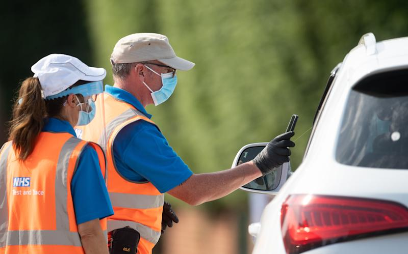 Staff scan the barcode on a coronavirus test through a car window at a mobile Covid-19 testing centre in Peterborough.