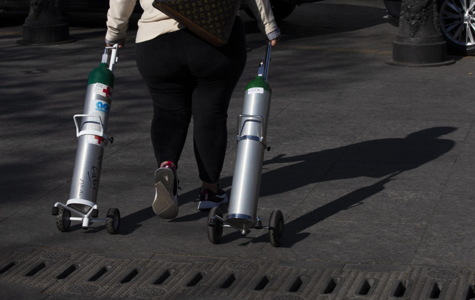 A woman walks off after refilling two tanks with oxygen for patients with COVID-19 in the Iztapalapa district of Mexico City, Tuesday, Jan. 26, 2021. The city is offering free oxygen refills for patients with COVID-19. (AP Photo/Marco Ugarte)