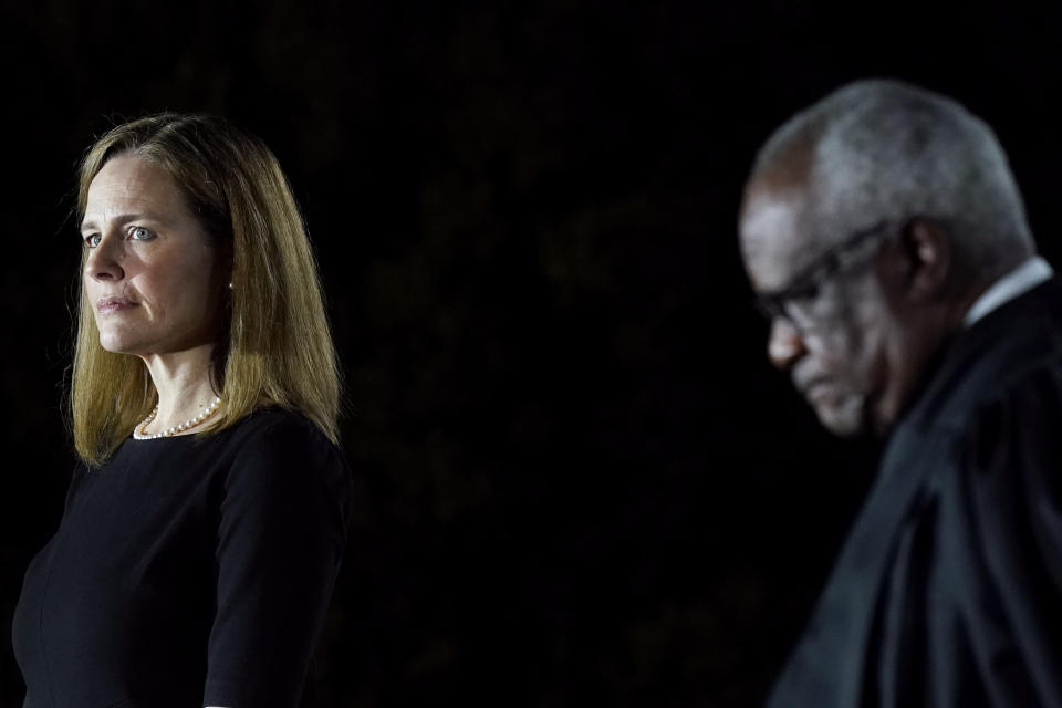 FILE - In this Oct. 26, 2020, file photo Amy Coney Barrett, left, and Supreme Court Justice Clarence Thomas listen as President Donald Trump speaks before Thomas administers the Constitutional Oath to Barrett on the South Lawn of the White House in Washington after she was confirmed by the Senate earlier in the evening. (AP Photo/Patrick Semansky, File)