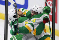 Minnesota Wild defenseman Matt Dumba (24) is congratulated by left wing Jordan Greenway (18) after scoring the winning goal against the Los Angeles Kings in overtime of an NHL hockey game, Saturday, Feb. 27, 2021, in St. Paul, Minn. (AP Photo/Andy Clayton-King)