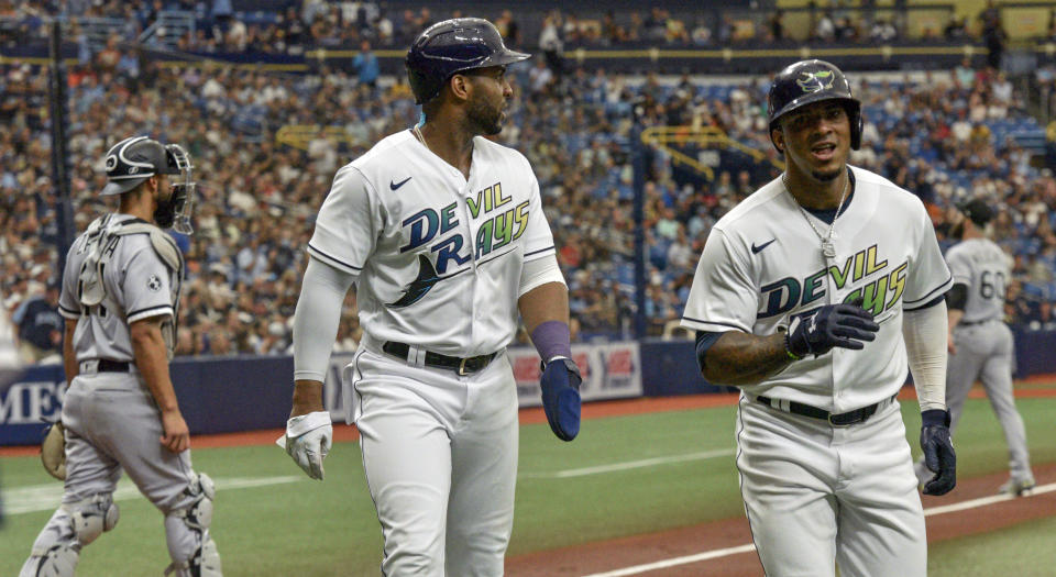 Tampa Bay Rays' Yandy Diaz, center, and Wander Cruz head for the dugout after scoring on an RBI-double hit by Brandon Lowe off Chicago White Sox starter Dallas Keuchel during the first inning of a baseball game, Saturday, Aug. 21, 2021, in St. Petersburg, Fla. (AP Photo/Steve Nesius)