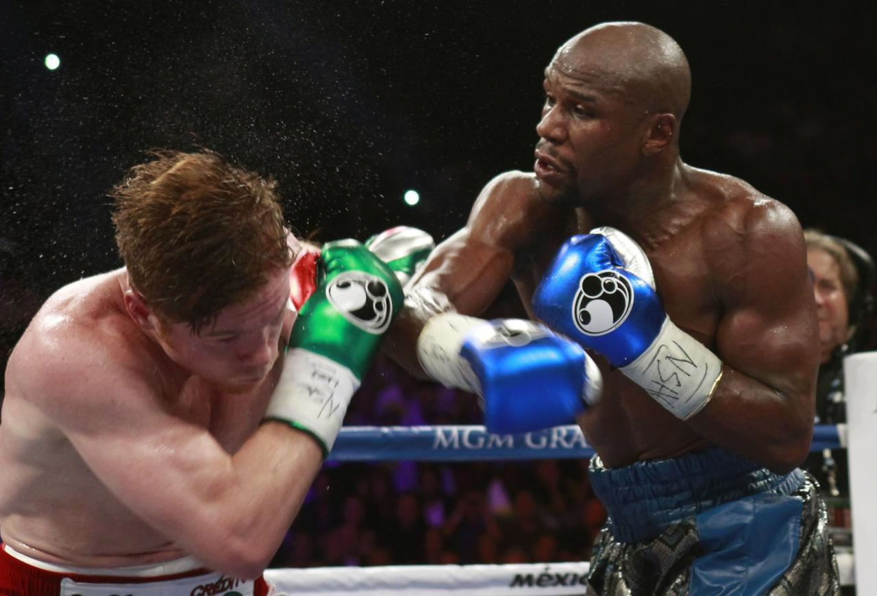 WBC/WBA 154-pound champion Canelo Alvarez (L) takes a punch from Floyd Mayweather Jr. of the U.S. at the MGM Grand Garden Arena in Las Vegas, Nevada, September 14, 2013. REUTERS/Steve Marcus (UNITED STATES - Tags: SPORT BOXING)